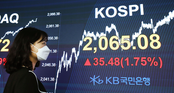 An employee looks at the Kospi displayed on a screen in the dealing room of KB Kookmin Bank, in the financial district of Yeouido, western Seoul, Monday. [NEWS1]
