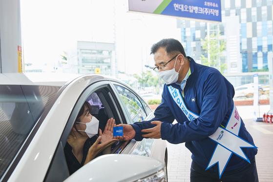 Hyundai Oilbank CEO Kang Dal-ho serves a customer at a branch in Gangnam, southern Seoul, previously owned by SK Networks. [HYUNDAI OILBANK]