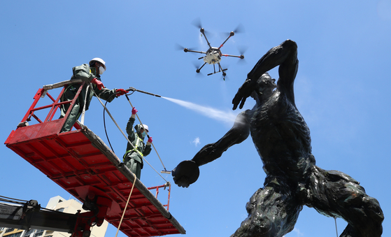 Officials from the Songpa District Office use drones and high-pressure power washers to clean an Olympic sculpture in Olympic Park in Songpa District, southern Seoul, on Monday. The district office cleaned 50 Olympic sculptures installed between Jamsil Sports Complex and Olympic Park on Monday. [YONHAP]
