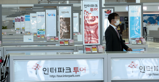 An employee waits in front of an empty counter inside Incheon International Airport Terminal 2 on Monday. According to data from market tracker FnGuide, the second-quarter operating profit for major local travel agencies is projected to drop more than 70 percent compared to the same period last year. [YONHAP]