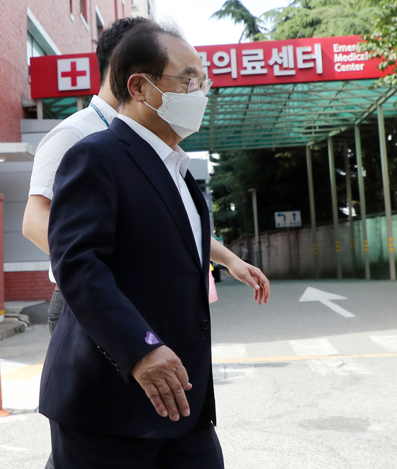Former Busan Mayor Oh Keo-don is beingtaken to an emergency room at a hospital in Busan on Tuesday. Oh complained offeeling something pressing on his chest while waiting in a police lock-up for acourt's decision on a detention warrant against him on a charge of sexuallymolesting a female civil servant. [YONHAP]