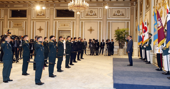 President Moon Jae-in, right, receives salutes from new lieutenant generals at a ceremony in the Blue House on Tuesday to celebrate their promotion. [JOINT PRESS CORPS]