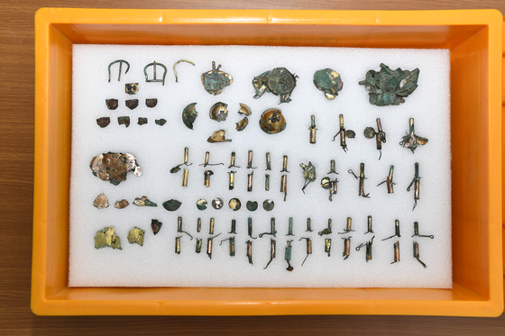 Parts of ornaments to what appears to have been a gilt-bronze saddle were excavated from tomb No. 120-2 in Gyeongju, North Gyeongsang, in May. [CULTURAL HERITAGE ADMINISTRATION]
