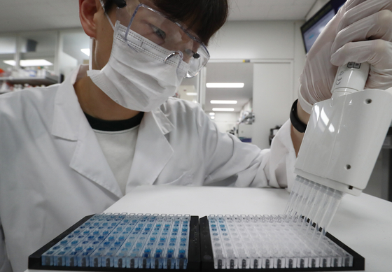 A lab researcher at the Korea Research Institute of Bioscience and Biotechnology demonstrates a Covid-19 antibody test kit at the institute in Daejeon on Tuesday. According to the lab, the test kit accuracy on those who have been infected was 94.4 percent, while the accuracy on confirming the negative status of subjects is 100 percent. The test only took 15 minutes. The Korean Ministry of Science and ICT plans to apply for Emergency Use Authorization from the U.S. Food and Drug Administration based on the test results. [NEWS1]