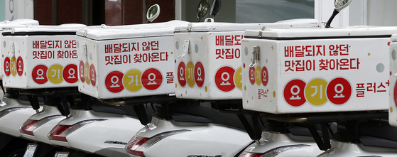 Yogiyo motorbikes are seen parked in Seongdong District, eastern Seoul, on Tuesday. Delivery Hero Korea, which operates Yogiyo, was fined 468 million won ($382,000) Tuesday for interfering in the management activities of restaurants. [NEWS1]