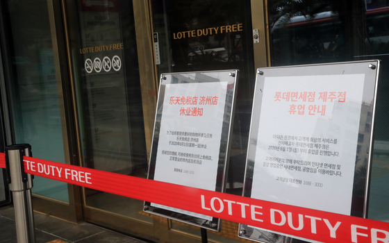 Signs informing customers of the closing of the store stand at the front door of Lotte Duty Free on Jeju Island on June 1. [YONHAP]