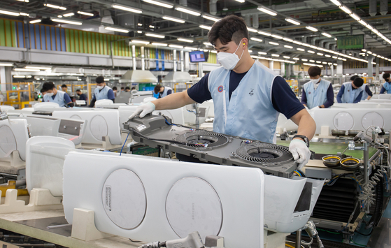 A worker assembles air conditioners at Samsung Electronics' plant in Gwangju, Gyeonggi, on Tuesday. The company said it is fully operating its air conditioner production lines as it expect a hot summer this year. Temperatures have been rising recently as the heat went up to as much as 28 degrees Celsius (82.4 degrees Fahrenheit) over the weekend, resulting in a sharp increase in sales. [SAMSUNG ELECTRONICS]