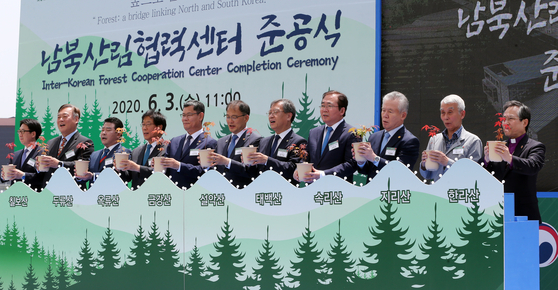 Unification Minister Kim Yeon-chul, fifthfrom left, and dignitaries celebrate the completion of an inter-Koreancooperation center on forestry in Paju, Gyeonggi, on Wednesday. [KIMSEONG-RYONG]
