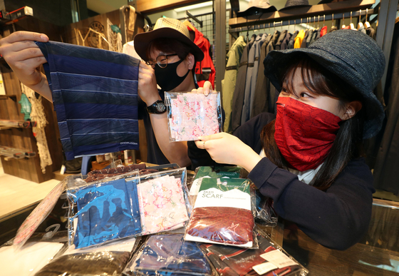 Customers examine scarves that can be used to cover their faces at Lotte Department Store's Daegu branch on Wednesday. On-year sales of multi-use scarves increased by 30 percent in May, as consumers seek protection from UV rays and airborne pathogens. [YONHAP]