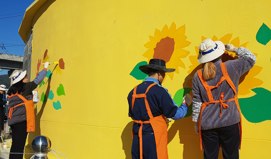 Volunteers paint the wall of a village in South Jeolla in November 2019. The government's third supplementary budget includes painting projects that will give temporary jobs to 8,500 artists. [South Jeolla Government