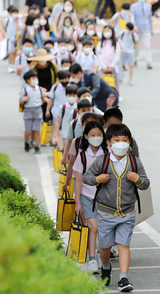 Students at Youngshin Elementary School in Daegu line up at school Wednesday as the third batch of nationwide students resumed normal classes for the first time since the pandemic struck. [NEWS1]