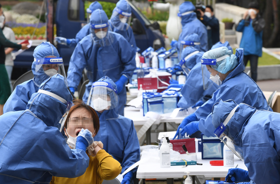 Officials at the Bupyeong District Office in Incheon get tested for the coronavirus Tuesday at a makeshift testing center on the office's front yard. The district office closed in the morning after two infections were detected among its employees. [NEWS1]