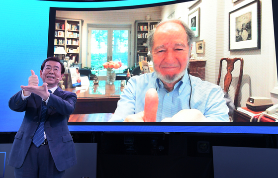 """Seoul Mayor Park Won-soon and Jared Diamond, author of """"Guns, Germs and Steel"""" (1997), make a hand gesture expressing thanks to front-line medical workers battling the coronavirus during a teleconference broadcast live from Seoul City Hall in central Seoul, Thursday. [SEOUL METROPOLITAN GOVERNMENT]"""