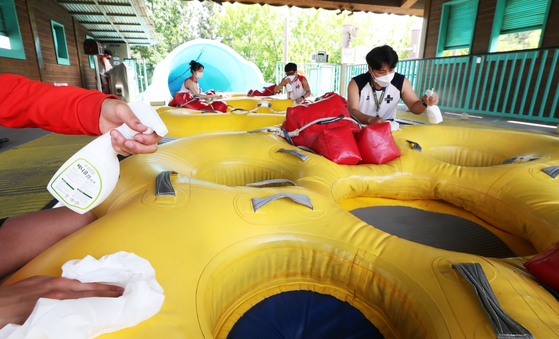 Employees from Everland, the country's largest theme park, disinfect the inflatable tubes used to ride down waterslides at Caribbean Bay on Thursday in Yongin, Gyeonggi. The water park will partially open starting Friday under strict social distancing measures. [YONHAP]