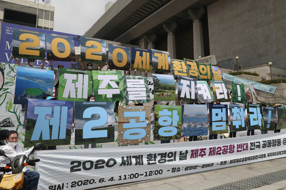 "Activists hold pickets that say ''2020 World Environment Month,' 'Save Jeju Island' and 'National Joint Action Against Constructing A Second Airport on Jeju Island'"" at a press conference held in front of the Sejong Center for the Performing Arts on Thursday. Civic groups and environmental activists are urging the government to completely scrap a plan to build a second international airport on Jeju Island due to concerns about the environmental impact. The conflict dates back to when the Ministry of Land, Infrastructure and Transport first announced the plan to build the airport in 2015. [YONHAP]"