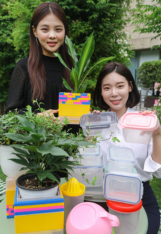 Models pose with plastic containers to promote Hyundai Department Store's campaign of collecting plastic to celebrate Environment Day on June 5. [HYUNDAI DEPARTMENT STORE]