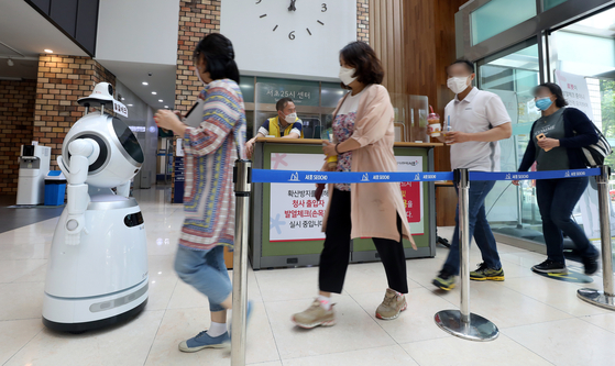 An artificial intelligence robot at the Seocho District Office in southern Seoul checks visitors' temperatures Thursday to look for signs of Covid-19 infection. The robot is also able to detect whether people are wearing their face masks correctly and give out audible instructions for those who aren't. [NEWS1]