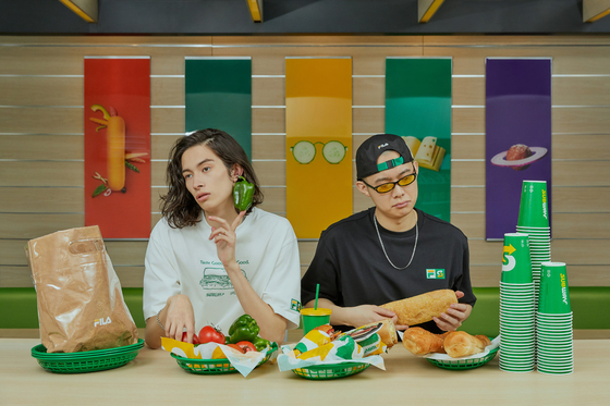 Models wear Subway-inspired clothes and eat sandwiches inside a Subway store. [FILA]