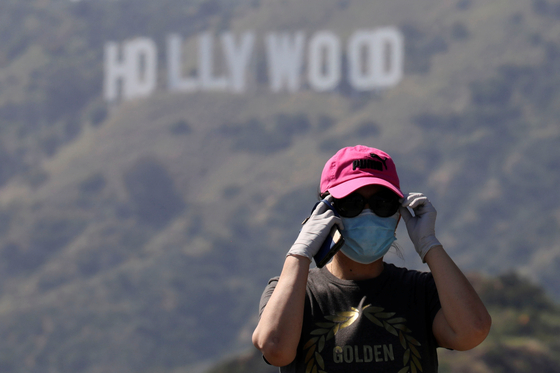 A person wearing a face mask and gloves stands in front of the Hollywood sign after a partial reopening of Los Angeles hiking trails during the outbreak of the coronavirus disease at Griffith Park in Los Angeles, May 9, 2020. [REUTERS/YONHAP]