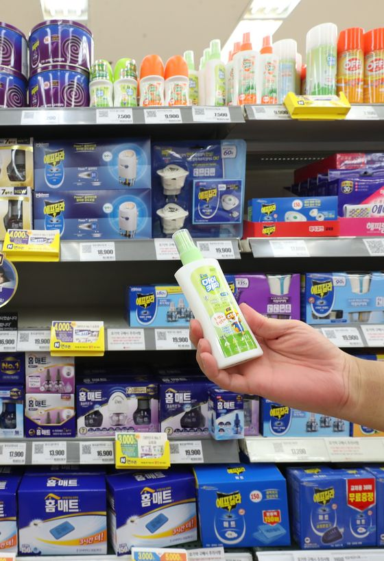 A customer picks up insect repellent at a discount store in Seoul on Monday. According to daily necessities chain Daiso, sales of insect repellent doubled in May compared to a month earlier. Experts predict people will see more insects this summer as a result of unusually warm temperatures last winter. [YONHAP]