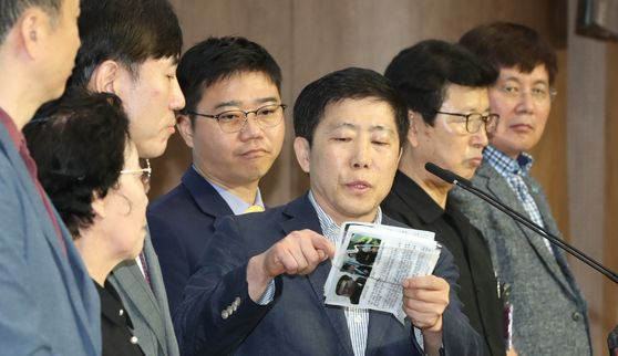 A South Korean right wing civic group leader, third from right, holds up propaganda leaflets his group sent to the North during a press conference with United Future Party lawmakers expressing opposition to a legal ban on the leaflets held at the National Assembly on Monday. [YONHAP]