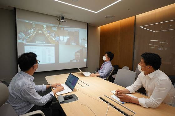 Lotte Duty Free workers hold a videoconference. The company started a telecommuting program for headquarters employees on Monday. [LOTTE DUTY FREE]