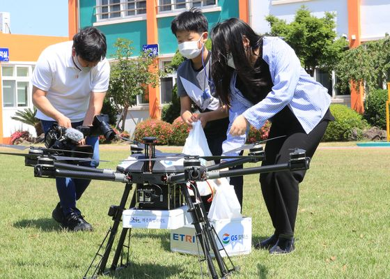 Students from Haeahn Elemenatry School on Jeju Island receive a box of sandwiches and snacks from convenience store GS25 delivered by a drone, on Monday. [YONHAP]
