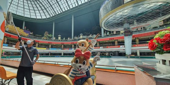 An employee cleans a pillar at Lotte World, located in Jamsil, western Seoul, Monday. The indoor theme park was closed Sunday after health authorities confirmed a coronavirus patient had visited the entertainment facility. It will reopen Tuesday. [YONHAP]