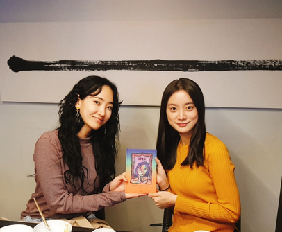 HA:TFELT, left, also known as Ye-eun, gifts her new book to Woo Hye-rim, right. Both were former members of Wonder Girls. [WOO HYE-RIM]