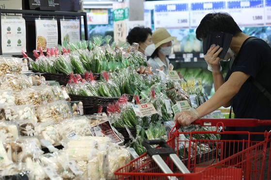 A shopper stands in front of the vegetable stand while wearing plastic gloves at a major mart in Seoul on Tuesday. Lately, food prices have been rising sharply as more people are eating at home. Prices are expected to rise further as the mercury rises. [YONHAP]