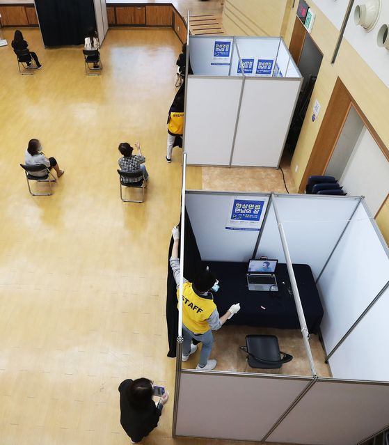 A Gwangmyeong city government employee sanitizes a booth where job seekers were interviewed by video at the city hall in Gyeonggi Tuesday. Because of the coronavirus pandemic, job interviews are mostly conducted in ways that do not require in-person meetings. [YONHAP]