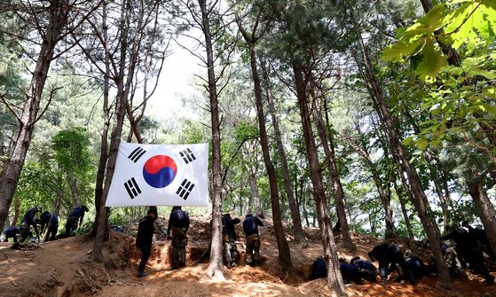 Soldiers excavate the remains of soldiers who died during the Korean War (1950-53) from a mountain in Hwacheon County, Gangwon, on Monday. [YONHAP]