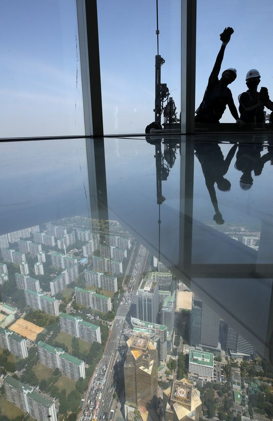 Workers clean the window of Lotte Tower, Korea's tallest building, in Jamsil, southern Seoul, on Tuesday. According to Lotte, it takes roughly 700 hours, or 90 days, to clean the whole building. [YONHAP]