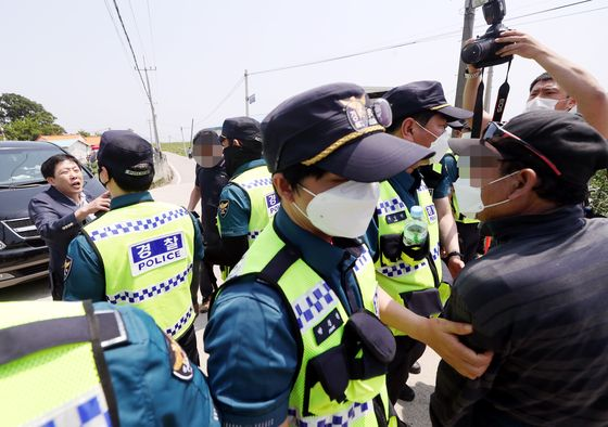 Park Sang-hak, head of Fighters for a Free North Korea, is blocked by local residents and police as the North Korea defector group tries to send rice in water bottles to the North from the coast of Samsan-myeon in Ganghwa County, Incheon, Monday. [YONHAP]