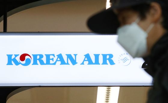 A masked passenger passes by in front of the Korean Air check-in counter at Gimpo International Airport's domestic flight office. [YONHAP]