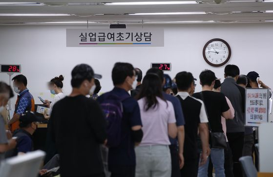 People line up at a job center in Jung District, central Seoul, on Wednesday to attend a presentation on how to apply for unemployment paychecks. [YONHAP]