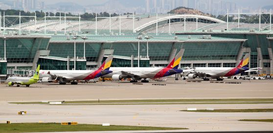 Asiana Airlines planes parked at Incheon International Airport on Wednesday. Korea Development Bank (KDB) released a statement on Wednesday in response to Hyundai Development Company's request to change the terms of its acquisition of the airline. KDB said HDC should be more specific about possible changes in terms. [YONHAP]