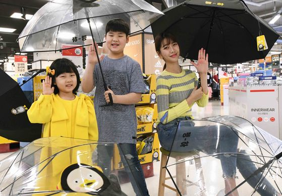 Homeplus models hold Pengsoo umbrellas at the Homeplus Gangseo branch in western Seoul on Wednesday. The product is a collaboration with the popular penguin character from EBS. Homeplus introduced Wednesday four new Pengsoo-themed umbrellas following the launch of Pengsoo-themed socks and slippers in March. [HOMEPLUS]