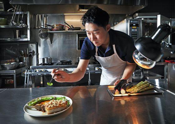 Chef Kim Jeong-ho of Sanok plates a dish in his kitchen. [PARK SANG-MOON]