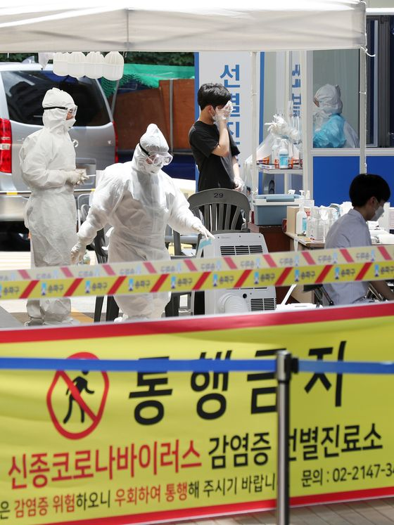 Quarantine officials conduct coronavirus testing on visitors at a makeshift testing facility at a public health center in Songpa District, southern Seoul. A total of 471 students and faculty at a cram school in the area were tested Tuesday after a cook at the school was found with the virus. [NEWS1]