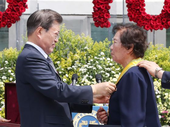 President Moon Jae-in, left, awards a Moran Medal to Bae Eun-shim, mother of the late student activist Lee Han-yeol, during the June 10 Democratic Protest anniversary ceremony on Wednesday.  [YONHAP]