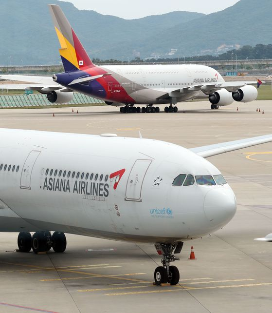 Asiana Airlines planes parked at the Incheon International Airport on Wednesday. The airline on Thursday rejected Hyundai Development Company's Tuesday statement blaming the airline for not providing sufficient information. [YONHAP]