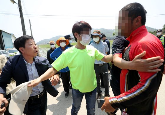 Park Sang-hak, a North Korean defector who heads the civic group Fighters for a Free North Korea, left, clashes with local residents of Ganghwa County, Incheon, after the residents stopped the organization from floating plastic bottles containing leaflets and propaganda across the coast into North Korea. [YONHAP]