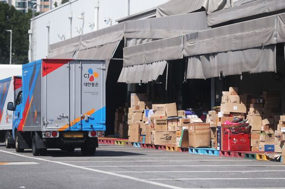 Packages piled up in front of the CJ Logistics terminal in Yeongdeungpo District in western Seoul, where a self-employed delivery person was confirmed to have contracted Covid-19 on Thursday. [YONHAP]