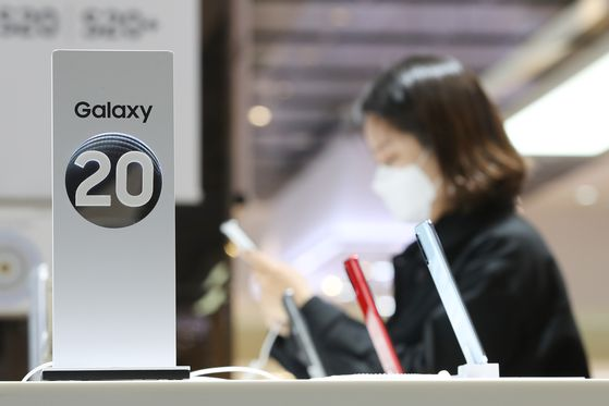 A customer checks out a smartphone at a Samsung store in Gangnam, southern Seoul, in late April. While semiconductor exports in May bounced back for the first time in three months, mobile phone exports including smartphones continued to fall due to the impact of the coronavirus pandemic. [YONHAP]