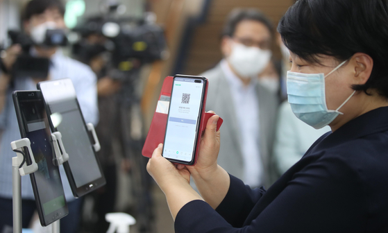 A member of a church in central Seoul is scanning a QR code on her phone before entering the church on June 2 to register her personal information with the KCDC. Similar registration is required at large churches, cinemas, noraebangs (singing rooms) and restaurants in Seoul, Incheon and Daejeon as a pilot program of KCDC to enable accurate tracing in times of an outbreak. [OH JONG-TAEK]