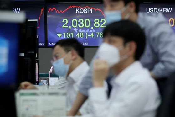 Employees sit in front of a screen showing the Kospi close in the trading room of Hana Bank in Jung-district, central Seoul, Monday. [YONHAP]