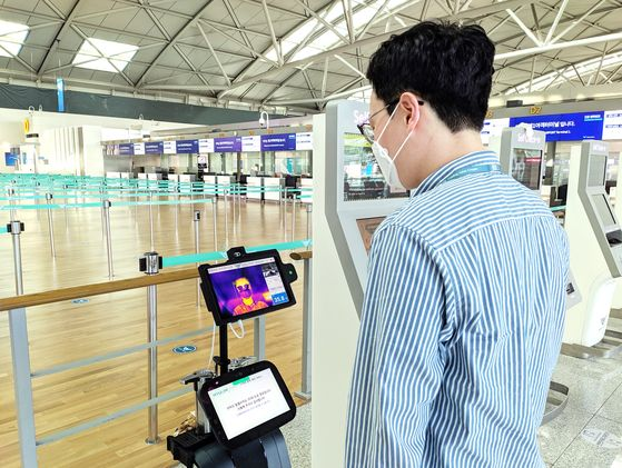 A volunteer tests a thermal screening robot at a departure terminal at Incheon International Airport on Monday. The Incheon International Airport Corporation on Monday announced it has set up thermal screening robots and kiosks where travelers and visitors can take their own temperature at both terminals. The robot automatically alerts the airline if a passenger's temperature is high, while the kiosk sets off an alarm. In the second half the airport plans to install a robot that detects whether a person is wearing a mask or not. [YONHAP]