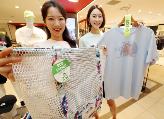 """Models pose with The North Face products that were made out of recycled plastic bottles at Lotte Department Store in central Seoul on Monday. According to the outdoor brand, its 'eco-collection"""" reduces energy consumption by 50 percent in the manufacturing process and reduces greenhouse gas emissions by 67 percent. [YONHAP]"""