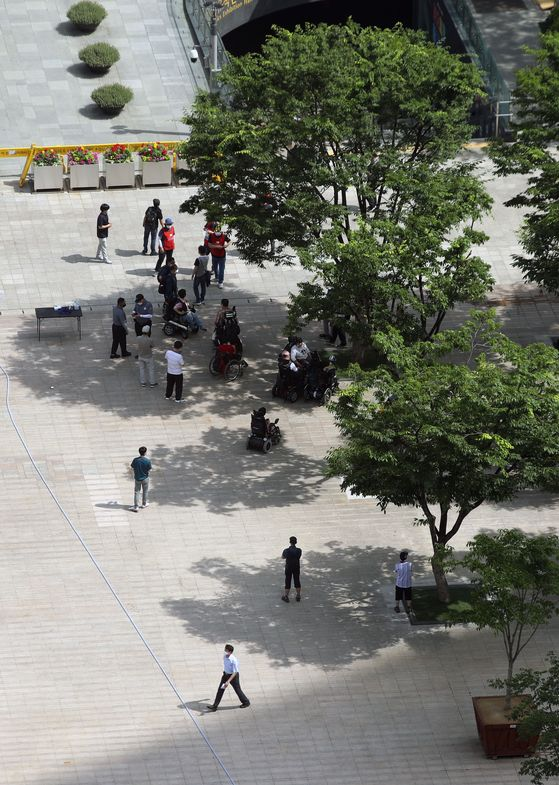 People stand under shade of trees to avoid direct sunlight at Seoul Plaza in front of Seoul City Hall on Monday during the heat of the day. [YONHAP]